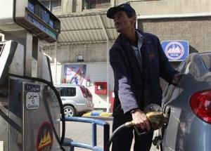 A worker pumps fuel at a petrol station in Cairo